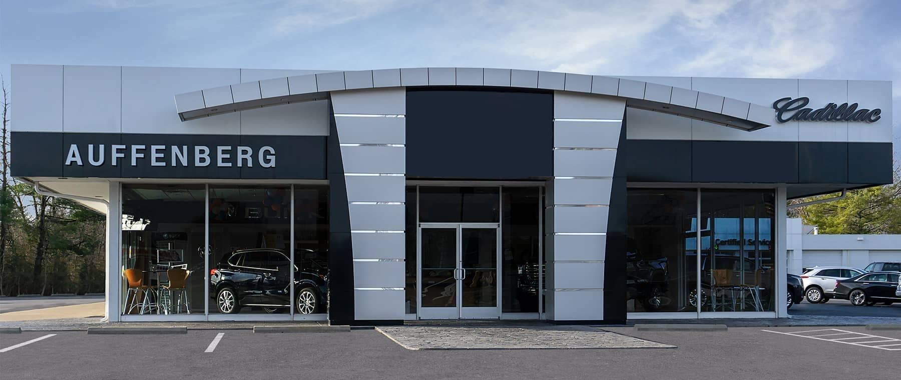 An exterior shot of a Cadillac dealership during the day