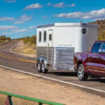 2019 RAM 1500 towing a trailer down a small hill on a paved road.