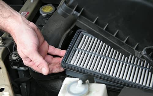 Mechanic replacing engine air filter