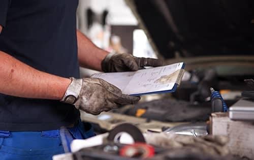 Mechanic checking clipboard