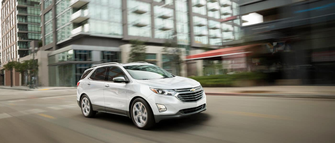 2021 Chevy Equinox driving down the road in a city