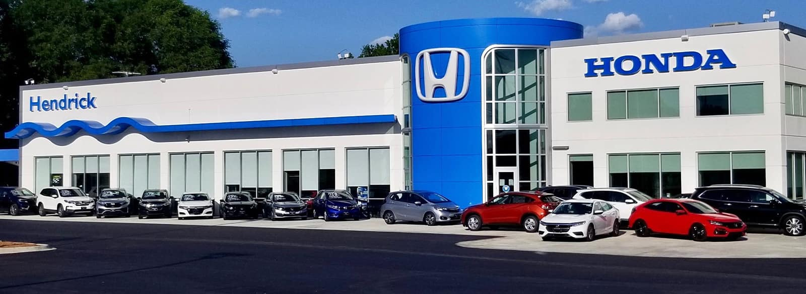 An exterior shot of a Honda dealership in the day.