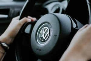 The driver holds onto a Volkswagen steering wheel, an genuine Volkswagen part.